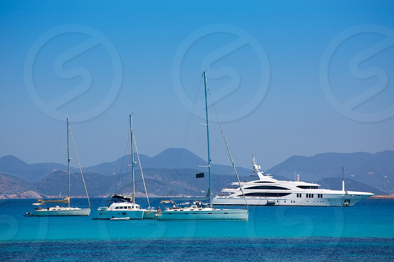 Ibiza coast view from Formentera with anchor boats in blue summer day photo
