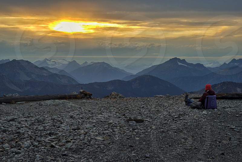 person sitting on hill top watching sun set photo