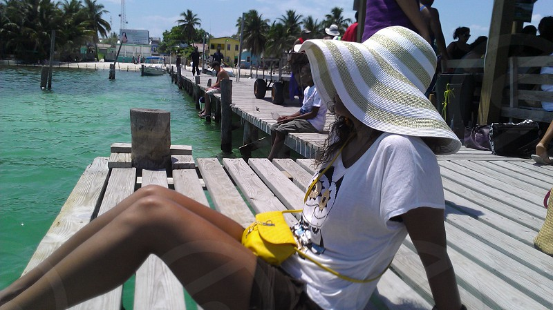Tropical Belize Caye Caulker sun hat pier Caribbean palm trees sea photo