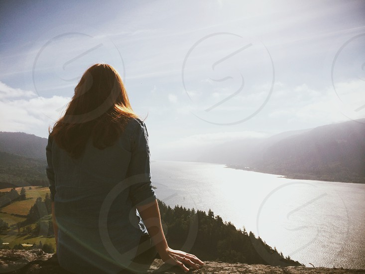 A young lady sits and looks out over a river. photo