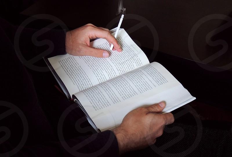 man holding white cigarette stick reading book photo