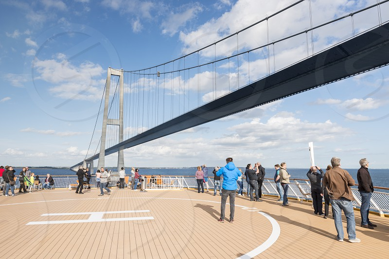 COPENHAGENDENMARK17-7-2017: Unidentified people on cruise ship crossing the great belt bridge on 17-July 2017: this bridge is a suspension bridge connecting the Zealand and Funen islands photo