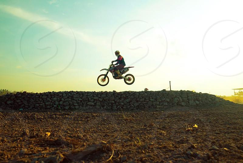 person riding on motorcross dirt bike making tricks during daytime photo