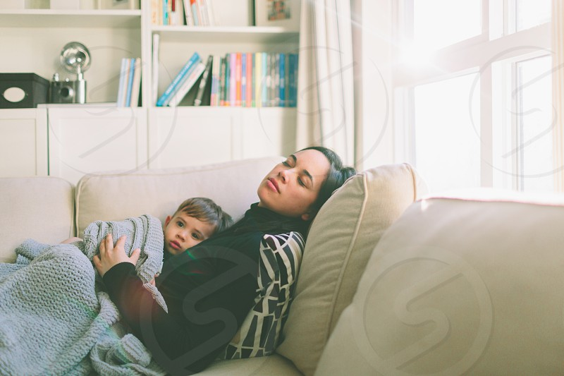 A mother sleeping on the couch while holding her toddler.  photo