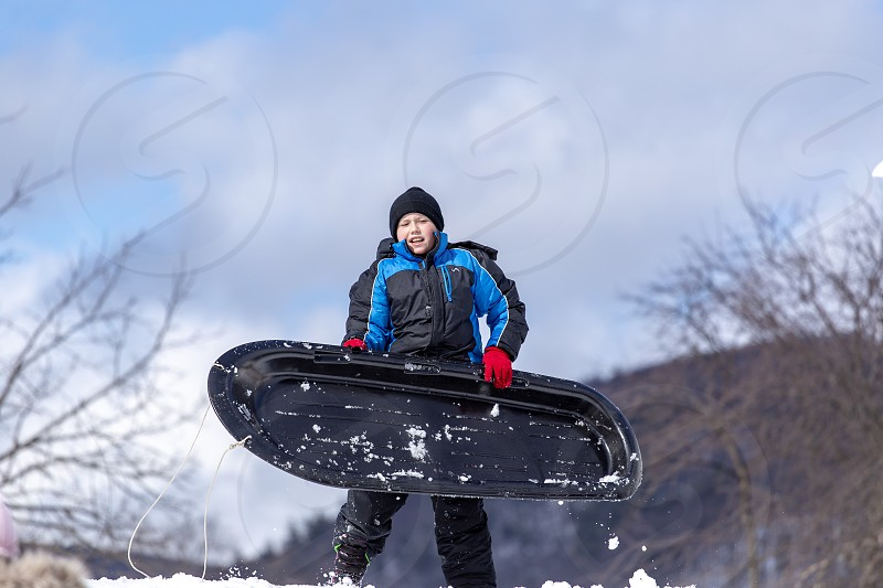 Boy getting ready to slide down the hill photo