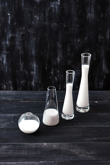 Containers of glass cone and spherical shape filled with white liquid on a dark wooden table on a black background with copy space. Milk saving technology. photo