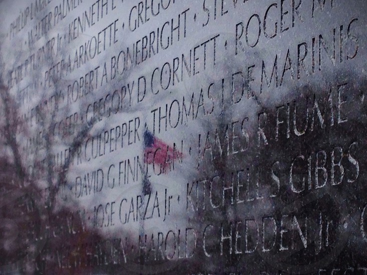 The American flag is reflected in the black granite if the Vietnam Veterans Memorial. photo