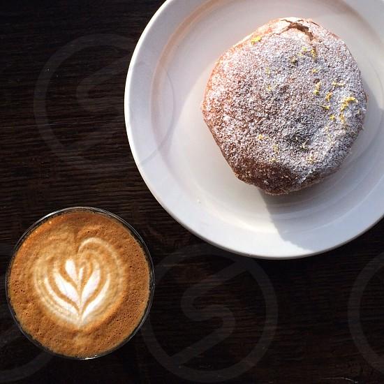 powder donut on white plate near foam heart latte on table photo