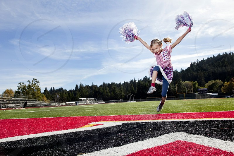 Cheerleader sports kids active school physical education after school activities pompons girl athlete child team football field jumping leaping excited supportive encouraging  photo