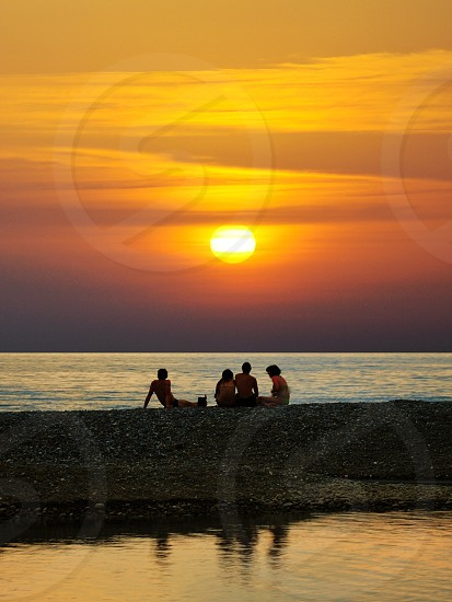 people at the beach during sunset photo