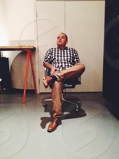 man in white and black checked shirt sitting on swivel chair photo