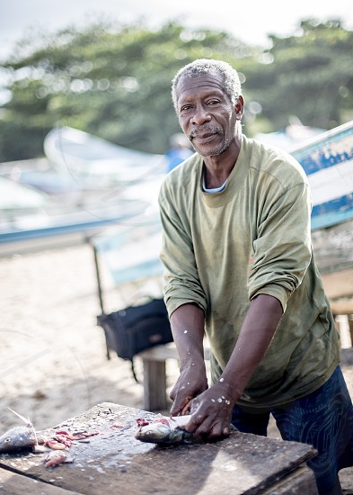 Fisherman cleaning fishes after a long morning in the ocean.  photo