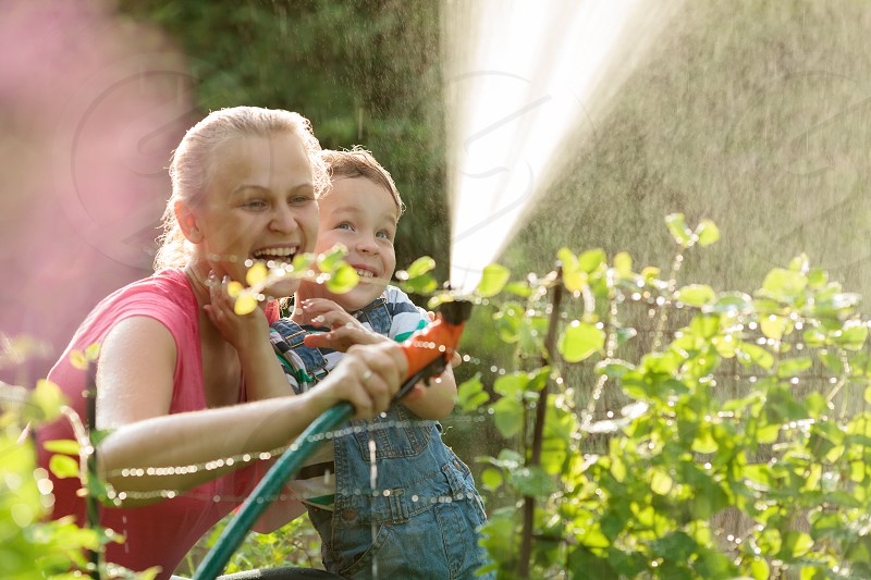 Young mother and cute son playing with water hose in the garden photo