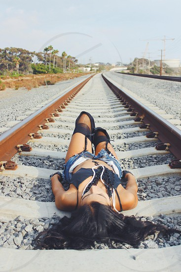 woman lying on train track photo