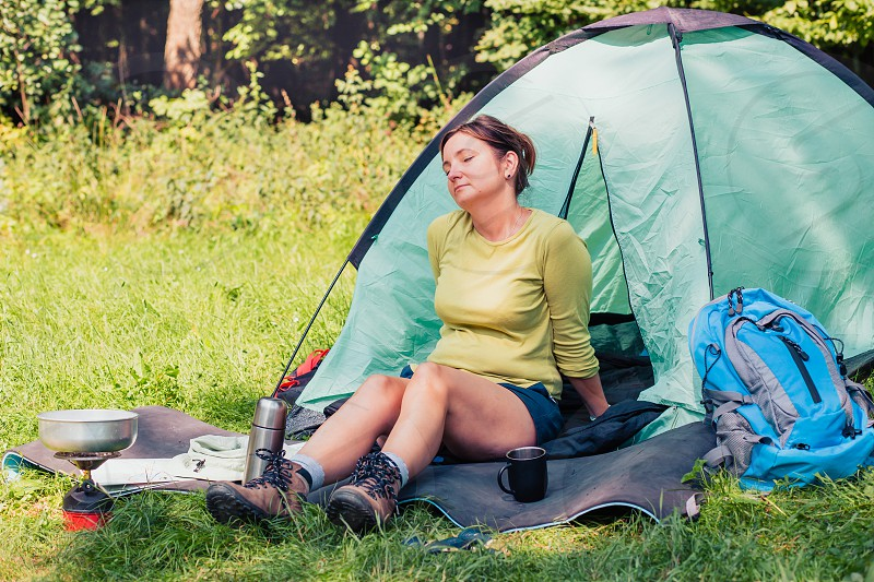 Spending a vacation on camping. Woman resting next to tent photo