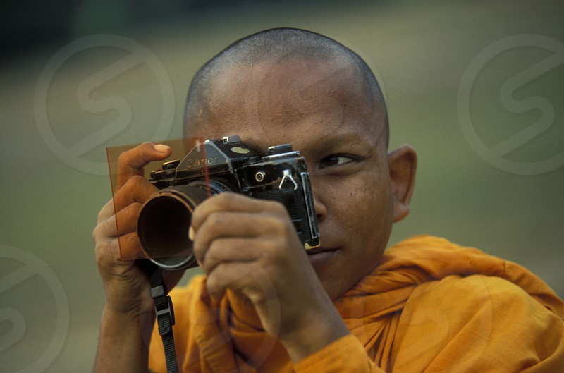 a monk take a pictures at the bayon temple in angkor Thom temples in Angkor at the town of siem riep in cambodia in southeastasia.  photo