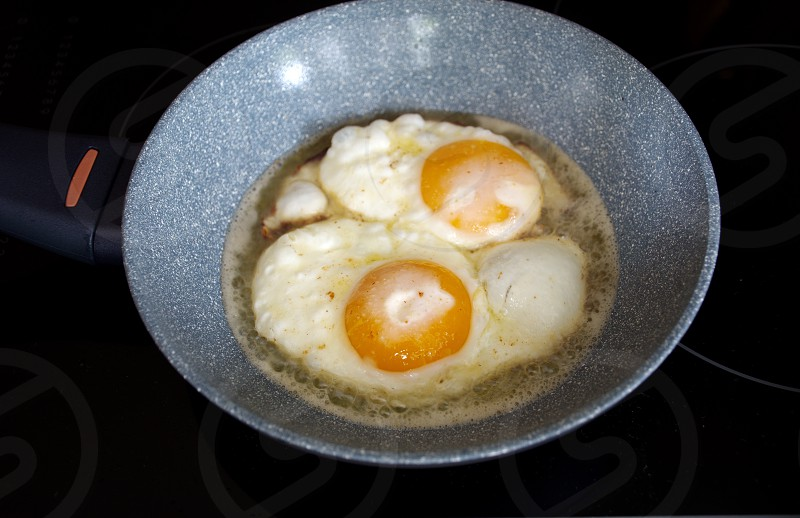 High angle view of the fried eggs in the pan on the stove photo