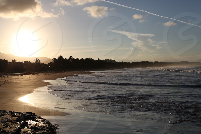 The sun begins to set on a deserted tropical beach. photo