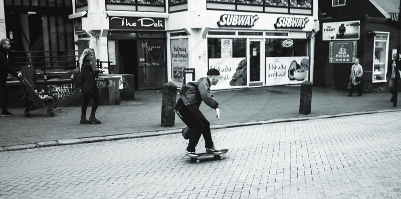 grayscale photo of man on skateboard near subway restaurant photo
