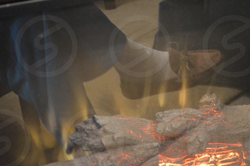 person in tan moccasins near fire pit photo