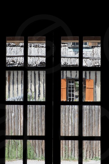 Old building through glass window. Panels. Geometric. Rectangles. Logs. Pattern. Cabin. Rustic.  photo