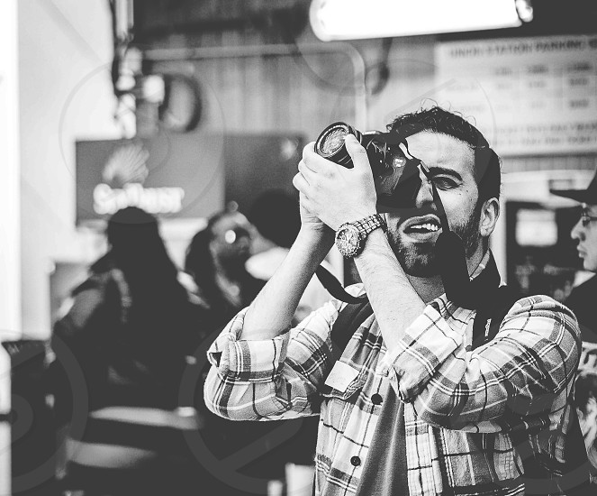 man aiming slr camera photo