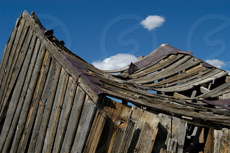 Old building. Roof. Weathered wood. Collapsing. Blue sky. Curve. photo