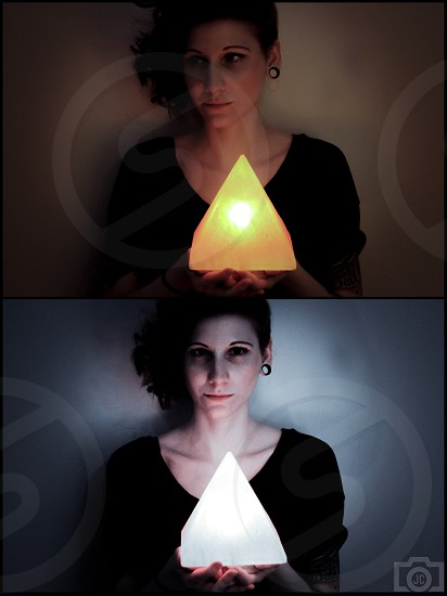 woman holding lighted triangle shaped lamp photo