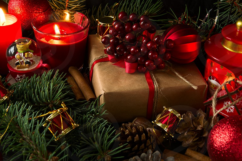 Christmas decoration with gift box baublesfir tree and burning red candles on dark wooden background. Low key photo