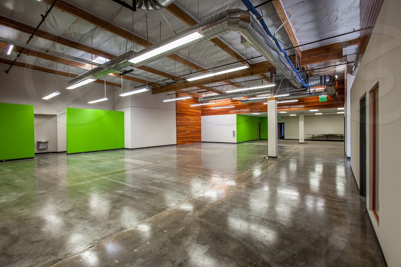 A contemporary modern office space. HVAC cables poured concrete green wood slats columns cat 5 lights drinking fountain polished reflection. photo