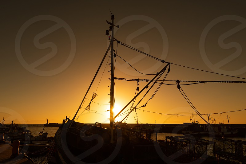 The sun rises behind a boat in Kalk Bay harbour in Cape Town South Africa. photo