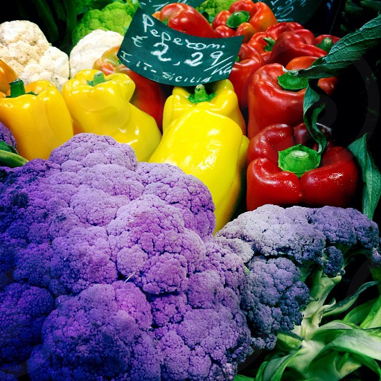 purple broccoli beside yellow and red bell peppers photo