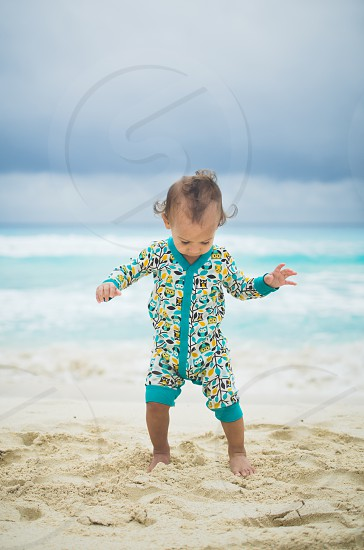 Baby walking on the beach looking downward wearing a colorful outfit. photo
