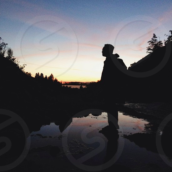 man in hooded jacket standing in darkness in stream photo