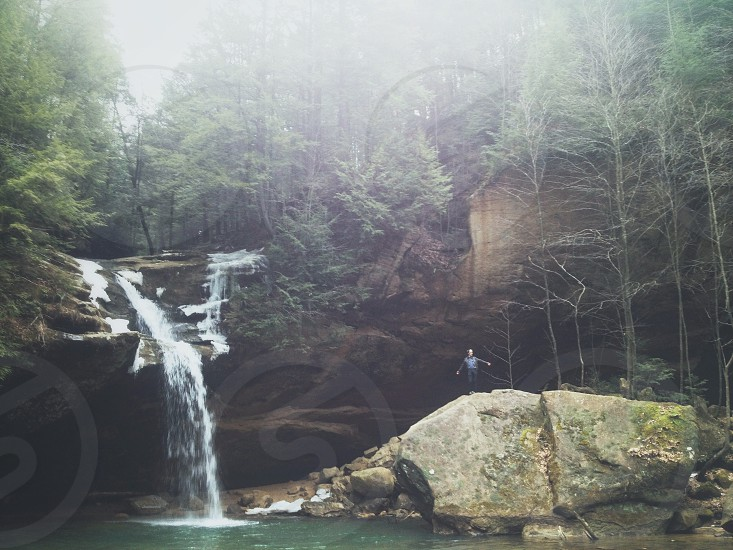 massive stone boulder under a water fall photo