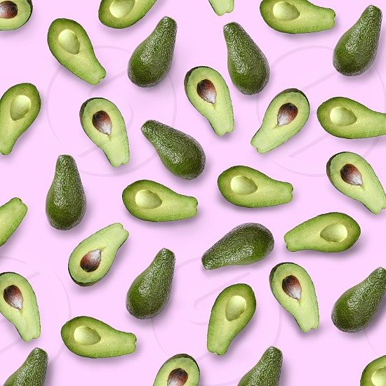 whole and halves of a green avocado on a pink background flat lay photo