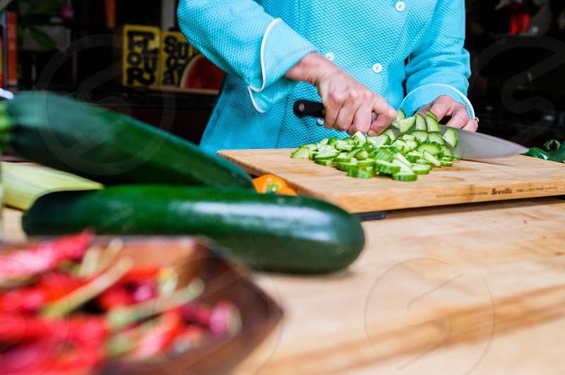 person in blue chopping zucchini on cutting board photo