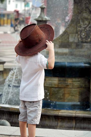 child on brown sun hat wearing white t shirt  near fountain photo
