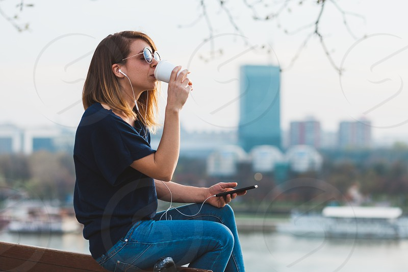 Young woman enjoying his coffee break listening to the music photo