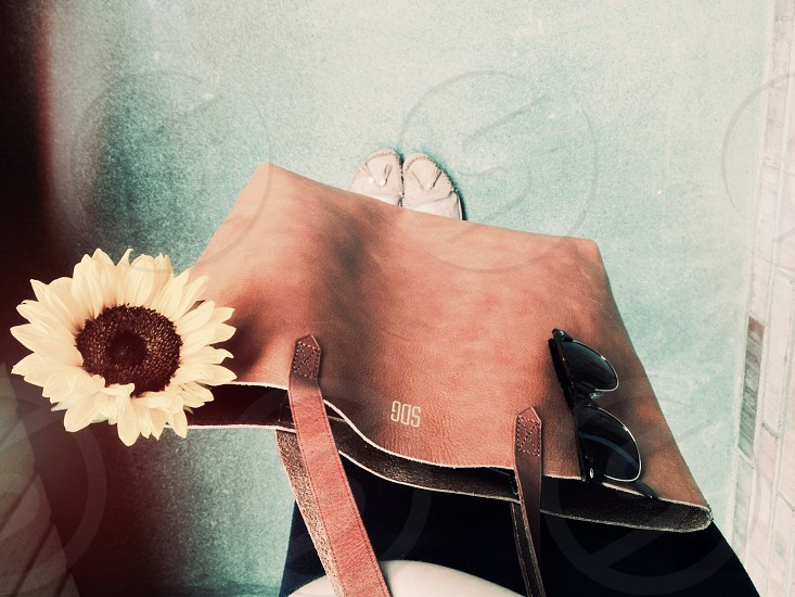 brown hand bag with yellow flower and black sunglasses photo