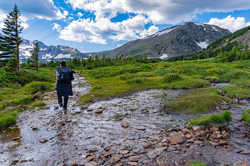 woman wearing back pack hiking along a trail that has turned into a stream. hiking the colorado rocky mountains photo