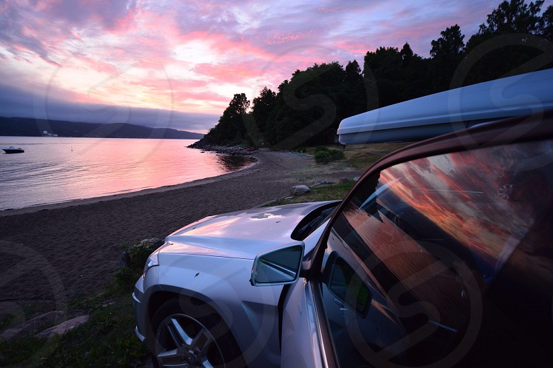 grey suv by grey sandy shore under blue sky during sunset photo