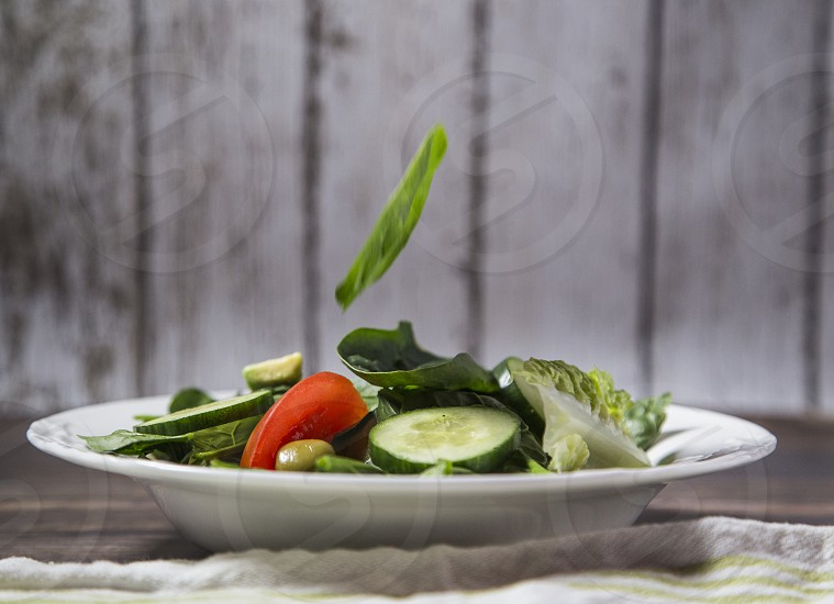 Green salad with tomatoes avocado green olives and cucumber photo