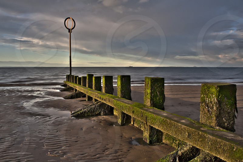 Beach at low tide with sea groin (sea wall wooden structure) at dusk.  Taken in Scotland photo