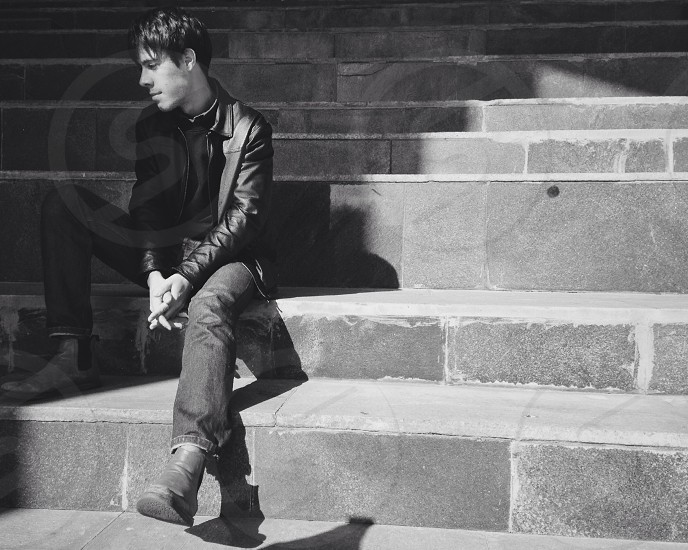 man in leather jacket and denim jeans sitting on concrete staircase photo