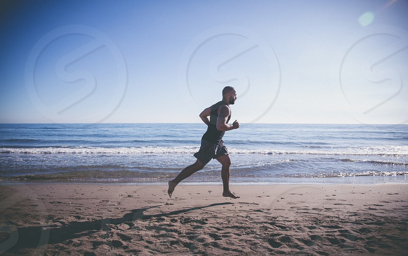 Young man is doing a run at the beach for his exercise photo