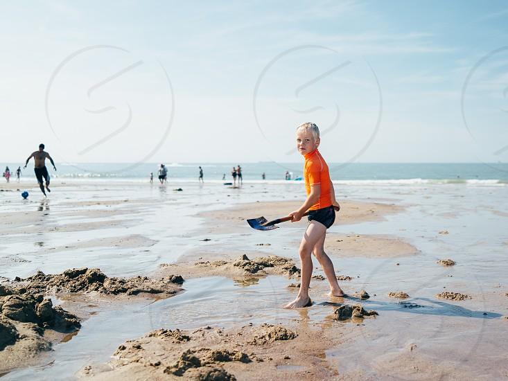 Summer fun at the beach.   Kid boy sun sand water play. photo