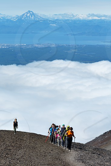 AVACHA VOLCANO KAMCHATKA PENINSULA RUSSIAN FAR EAST - AUGUST 7 2014: Hiking on Kamchatka - group of tourists and travelers climbing to top of Avachinsky Volcano on background of Avacha Bay and volcano. photo