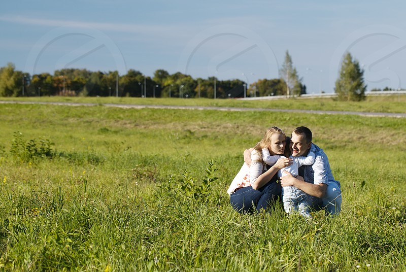 Mother father and their little son having fun in the countryside. Son hugs and kissing his father and mother as they laugh and frolic enjoying the fresh air and sunshine photo