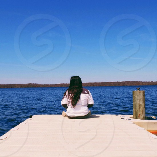 person seating on a wooden bridge by a sea photo